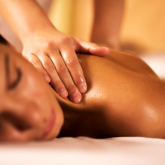 Young woman in the spa receiving back massage. Focus is on human hands.