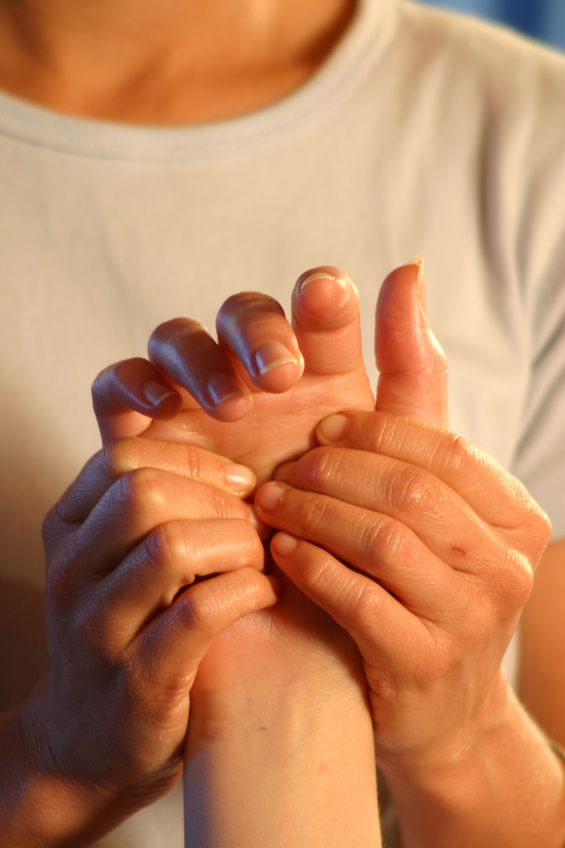A massage therapist working on a reflex point in the palm of the hand.