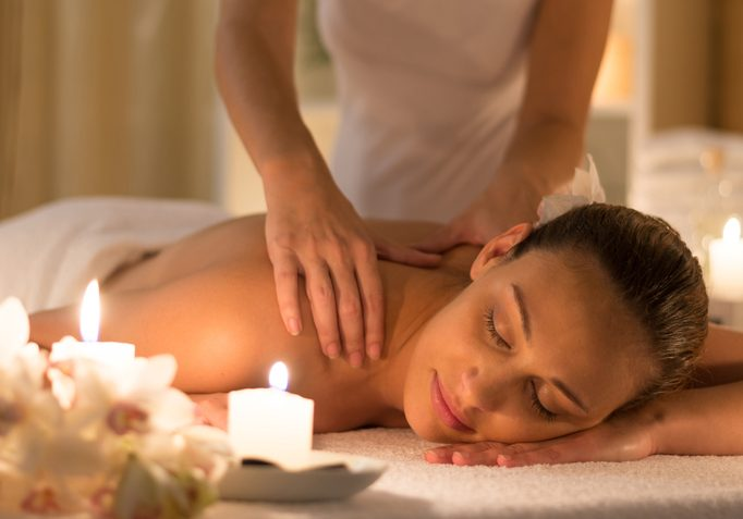 Woman receiving shoulder massage at spa and beauty salon / candle light